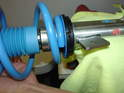As you can see here, the end of the coil spring sits flush on the blue spacer ring on the top edge of the spring perches.