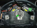 In the center of the steering wheel is a 16mm bolt that secures the wheel in place (green arrow).