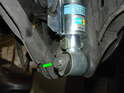 Pull the grommets holding both the ABS sensors and brake lines out of the rear shocks and remove the lower shock mounting bolts (green arrows).