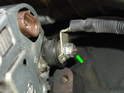 Now remove the 10mm nut holding the 12v lead wire to the back of the alternator (green arrow).
