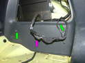 Remove the two Phillips head screws holding the trim panel to the side of the car (green arrows).