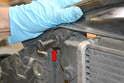 With the center plug out you can pull the base of the plug out and this will free up the radiator (red arrow).