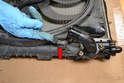 Lift up on the bottom two clips and this will allow the shroud and fan to slide up and off the radiator (red arrow).