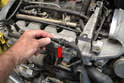First disconnect the knock sensor plug by squeezing the metal clip and pulling the wiring connections apart (red arrow); now remove most of the front of the vehicle.