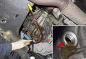 Using a fluid pump (blue arrow), fill the transmission until fluid flows out of the fill plug hole (red arrow).