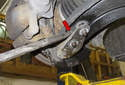 Next, you have to lever the ball joint bracket away from the control arm (red arrow).