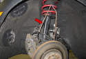 Remove the caliper and suspend it using a bungee cord or stiff wire (red arrow).