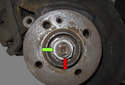 Lever the folded portion of the nut away from the axle shaft end (red arrow).