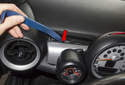 Using a plastic prying tool (red arrow), lever the left side instrument panel trim off the instrument panel.