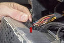 Disconnect the main connector by squeezing the clip and moving the lever (red arrow) down until the connector is out of the radio.