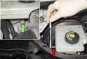 Using an E7 Torx bit socket (red arrow), remove the brake fluid reservoir-mounting bolt (green arrow).