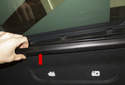 Working at the headliner sunroof plastic trim, unclip it at the top, roll it downward and detach it from the body (red arrow).
