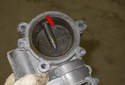 Once you have removed the throttle body, check for oil or dirt build up (red arrow) on the throttle plate.