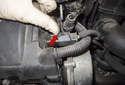 Exhaust camshaft sensor: Working at the front of the cylinder head, disconnect the camshaft sensor electrical connector by pushing up on the release tab (red arrow) and pulling it straight off.