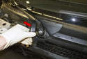 Working at the right and left side wiper arm pivots, remove both plastic caps (red arrow) by pulling them straight up.