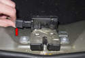 Working at the tailgate latch, disconnect the electrical connector (red arrow) by pressing the release tab and pulling it straight off the latch.