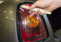 To replace the lens or bulbs with the lens removed, start by removing the trim around the taillight.