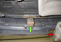 Working at the bottom center of the rear bumper just to the right of the tailpipe (red arrow), remove the 8mm fastener (green arrow).