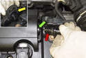 Working at the valve cover, install the supplied hose adapter (red arrow) into the hose connection (green arrow).