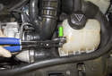 Using a pair of hose clamp pliers, remove the vent hose clamp (green arrow).