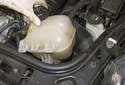 Detach the expansion tank from the radiator support by lifting the rear up then removing it from the radiator support.