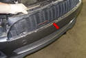 Slide the grille straight off the radiator support to remove (red arrow) it.