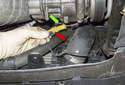 Working at the A/C compressor, slide the electrical connector off the compressor (green arrow).