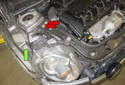 Working at the right side of the engine compartment, remove the 10mm headlight fastener (green arrow).