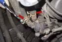 Then using hose clamp pliers, remove both coolant line hose clamps (red arrows).