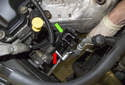 Working at the oxygen sensor electrical connector mount (green arrow), remove the 10mm fattener (red arrow).