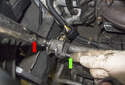 Using a 21mm wrench, rotate the drive belt tensioner clockwise (red arrow) and press the retaining pin (green arrow) in to hold it in place.