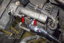 Working at the drive belt tensioner, remove the two E10 external Torx (red arrows).