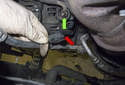 Working at the top left of the alternator, disconnect the electrical connector by pressing the release tab and pulling it off (red arrow).