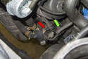 Working at the auxiliary coolant pump, detach the wiring from the bracket (green arrow), and then disconnect the electrical connector (red arrow).