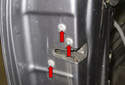 Remove the three T30 Torx door latch fasteners (red arrows).