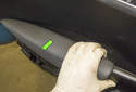 Grab the armrest cushion and pull the top away from the door panel (green arrow), pulling it up and away to detach the clips.
