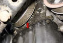 This photo shows an oil leak at the right side of the engine, surrounding the crankshaft pulley (red arrow).