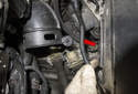 Move to the left side of the intake air housing and unclip the vacuum line (red arrow).