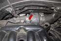 Working at the center of the intake manifold near the firewall, remove the T20 Torx screw (red arrow).