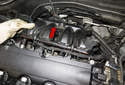 Slide the intake manifold away from the cylinder head enough to access the components beneath it (red arrow).