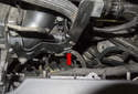 Working at the left side, detach the wiring harness mounting clip (red arrow) from the manifold.