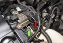 Remove the wiring harness housing (red arrow) from the mounting bracket (green arrow) by sliding it straight up.