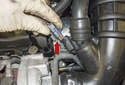 Working at the crankcase breather heating element, release the tab (red arrow) and disconnect the electrical connector.