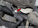 Follow the line down to the subframe, then press the release tab (red arrow) and pull the line straight off.