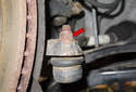 Working at the outer tie rod, remove the 18mm tie rod end nut (red arrow).