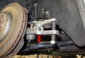 Using a ball joint separator (red arrow), remove the tie rod end from the steering knuckle.