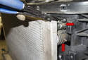 Working at the left side of the radiator, tilt the top of the radiator out of the vehicle.