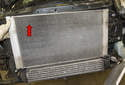 To remove the radiator, pull it out of the radiator support upward and out of the radiator support (red arrow).