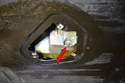 Place a large catch pan under the engine and remove the 15mm oil drain plug (red arrow).