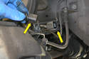 Disconnect the wear sensor from the harness (yellow arrows) and remove it from its retaining clip on the caliper mount.